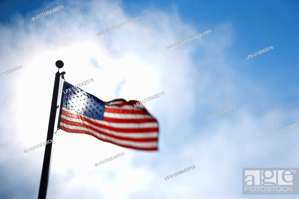Stock Photo: American flag blowing in breeze against blue sky.