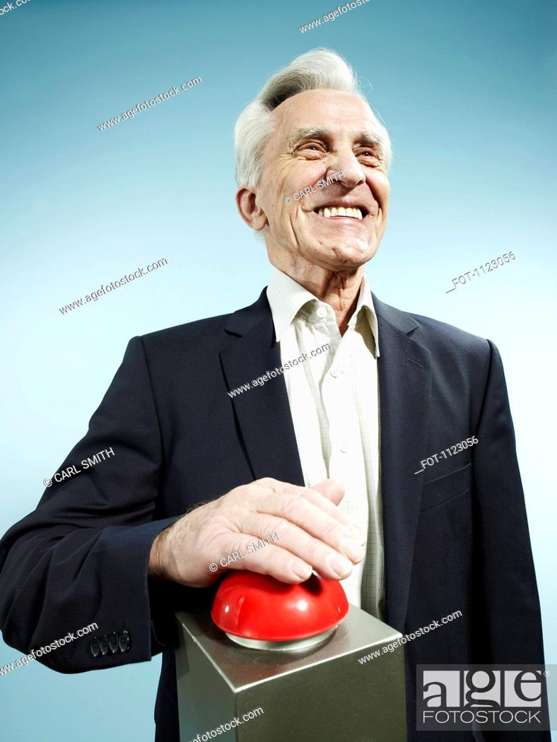 Stock Photo: A grinning senior man pushing a red game show buzzer.