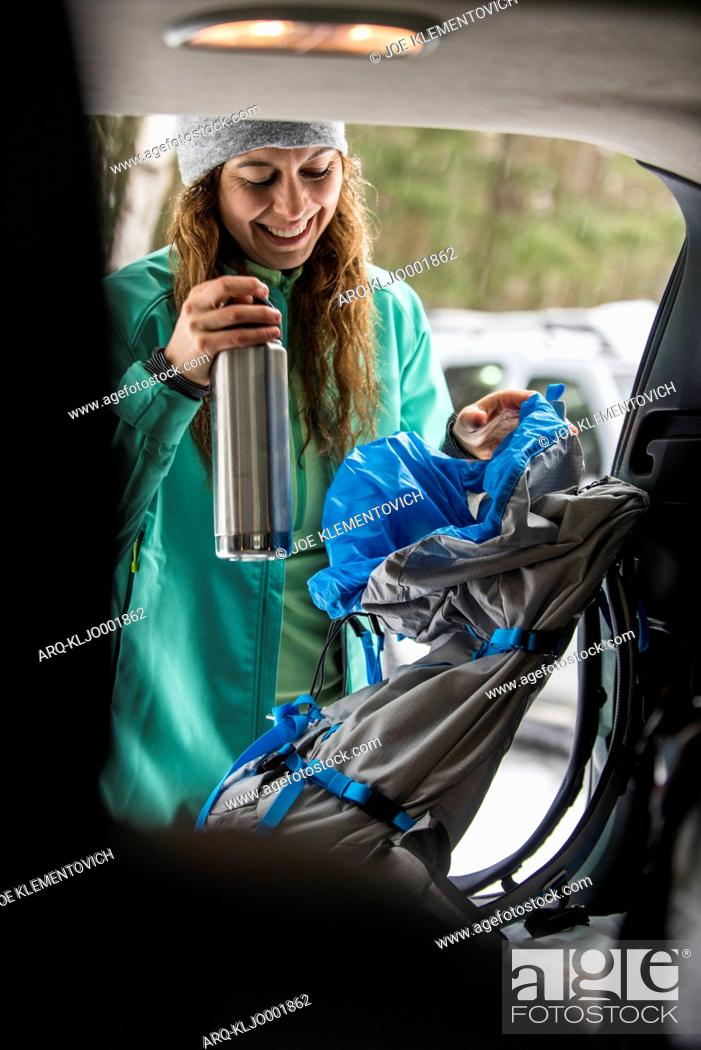 Imagen: Woman snowshoer preparing in the back of a car.