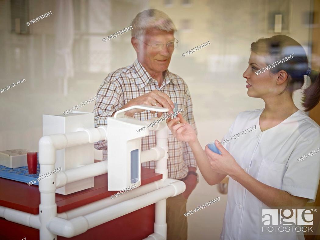 Stock Photo: Germany, Cologne, Caretaker giving medicine to senior man in nursing home.
