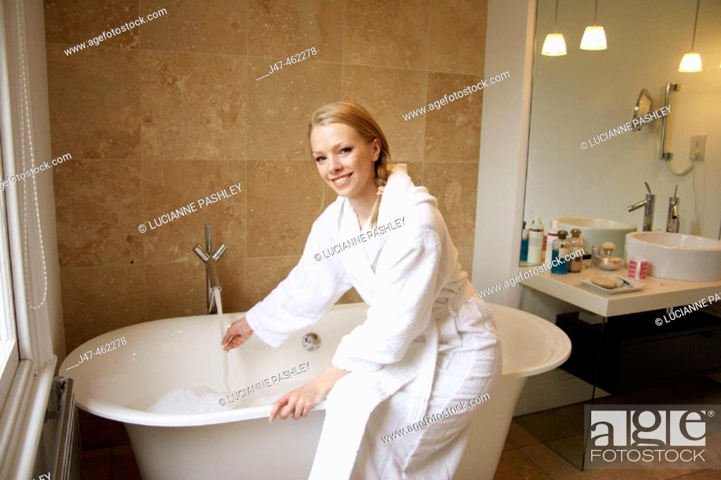 Stock Photo: 21 year old girl sitting on  the edge of the bath, smiling, holding her hand under the water.