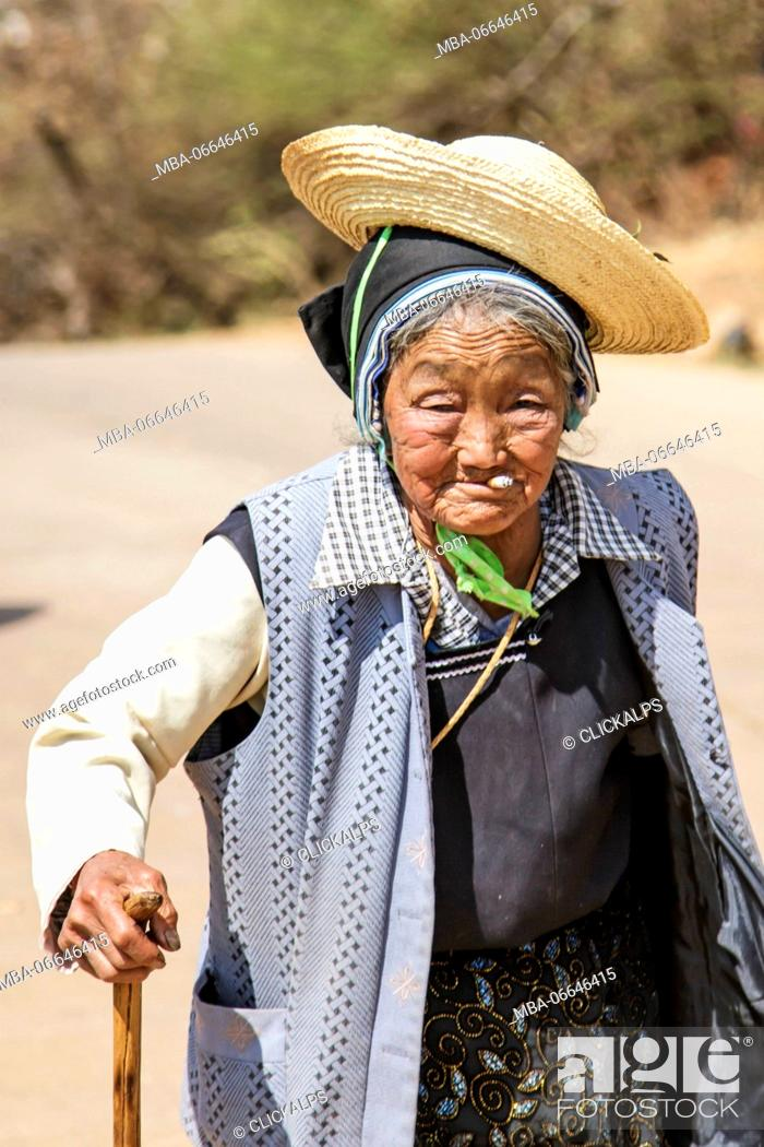 Stock Photo: Old Chinese woman dressed with traditional Bai clothing during the Heqing Qifeng Pear Flower festival, China.