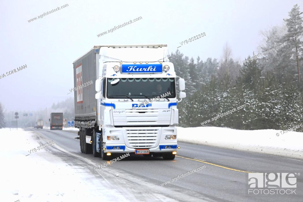 Stock Photo: Beautifully customized DAF XF 105 truck of J Kurki hauls Freja cargo trailer along highway in winter in Raasepori, Finland - February 9, 2018.