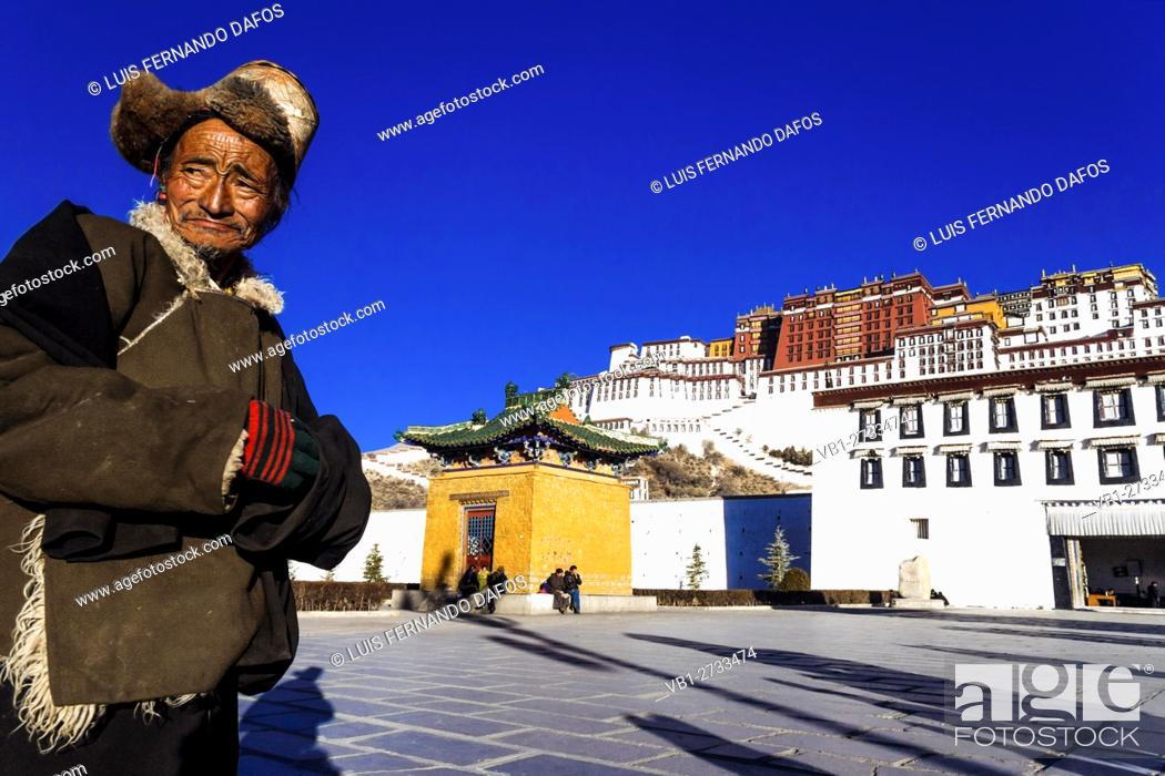 Stock Photo: Old Tibetan man with fur hat standing in front of Potala palace in Lhasa, Tibet, China.