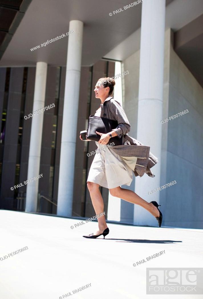 Stock Photo: Businesswoman running outdoors.