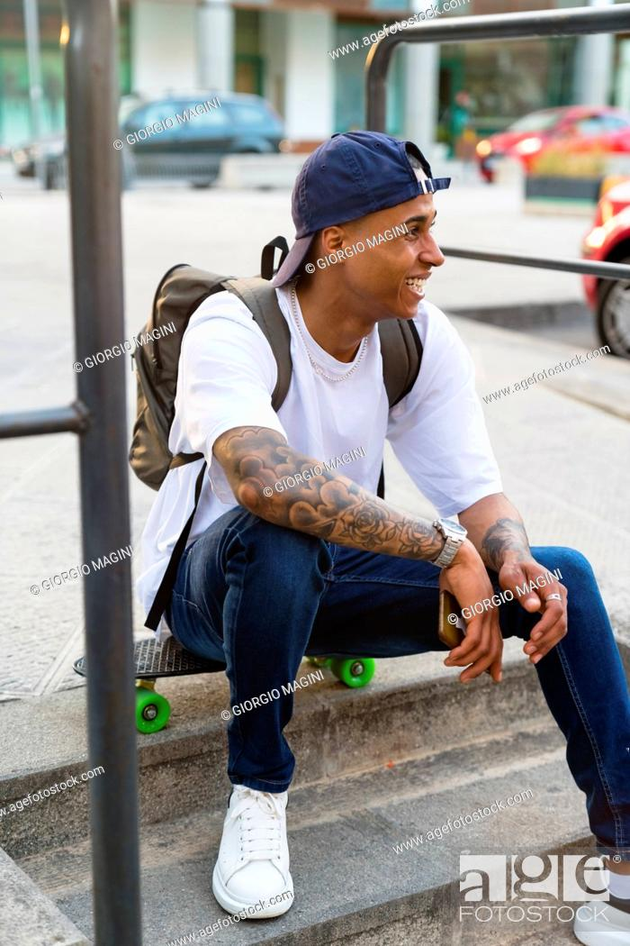 Stock Photo: Tattooed young man with backpack and smartphone sitting on skateboard looking at distance.