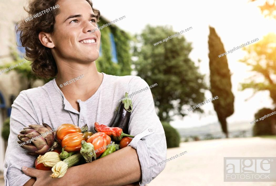 Stock Photo: Italy, Tuscany, Magliano, Young man holding variety of vegetables, smiling.
