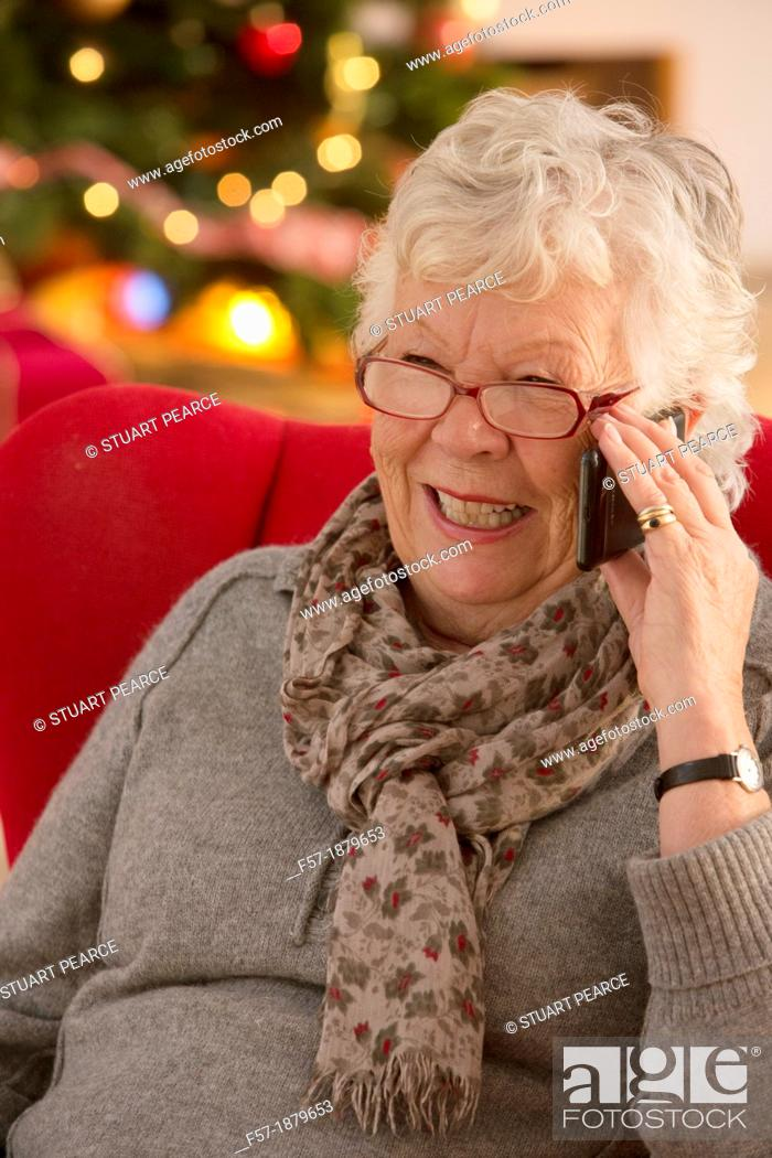 Stock Photo: Senior woman communicating with family on her smart phone at Christmas time.