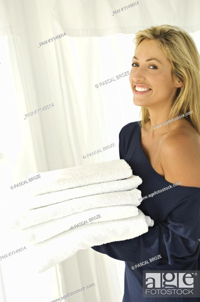 Stock Photo: Young woman carrying stack of towels.