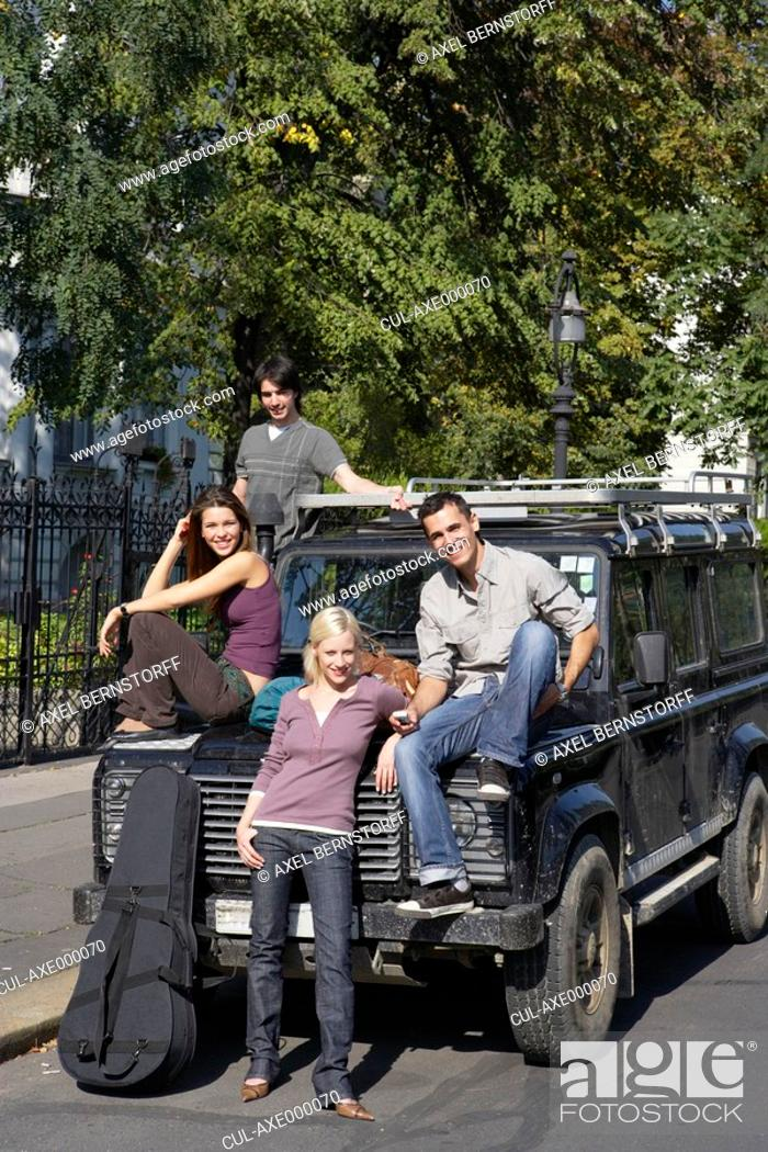 Stock Photo: Four friends with an SUV and a guitar smiling.