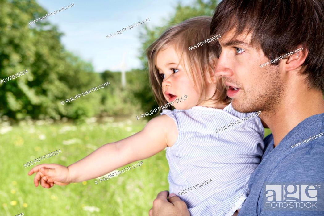 Stock Photo: Germany, Cologne, Father and daughter in meadow.