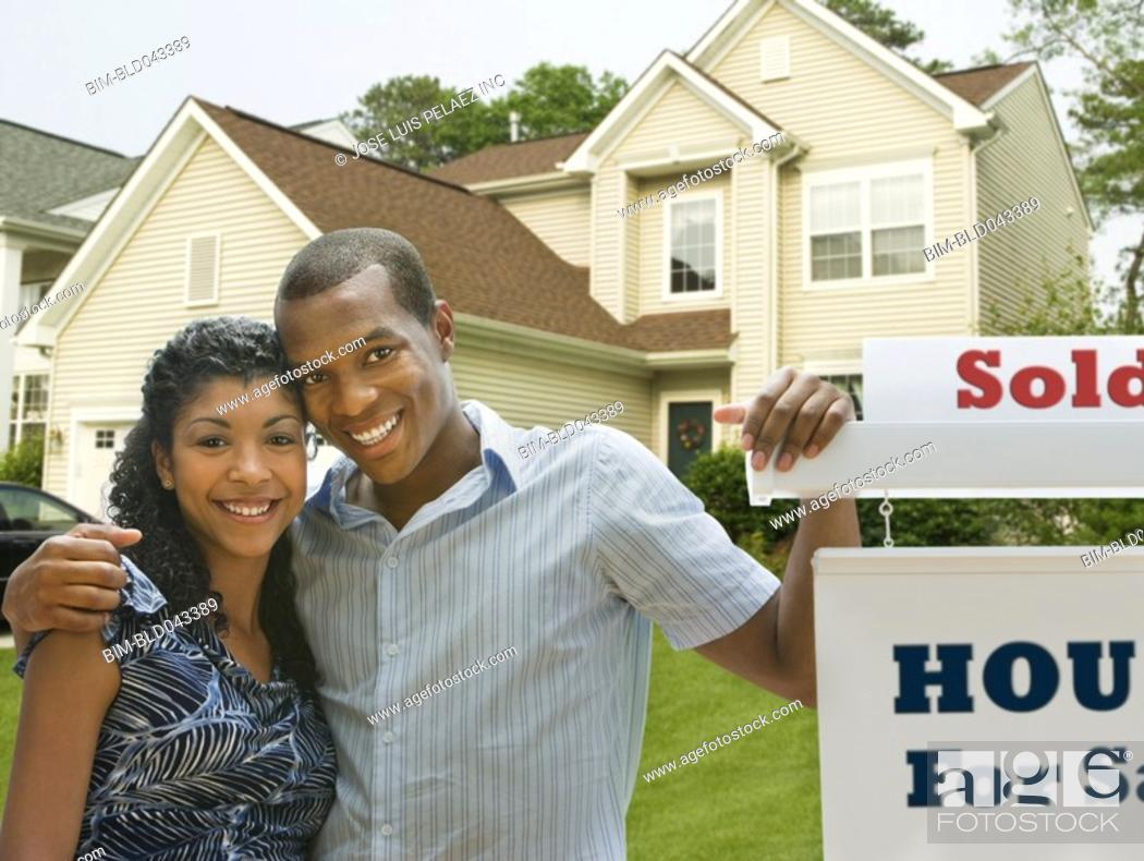 Stock Photo: African American couple in front of new house.