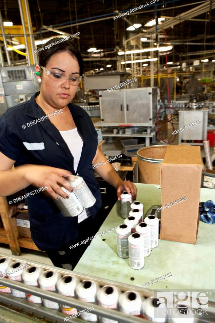 Stock Photo: Hispanic worker packing boxes in factory.