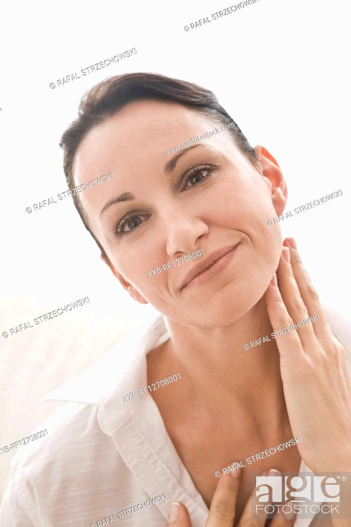 Stock Photo: woman creaming neck.