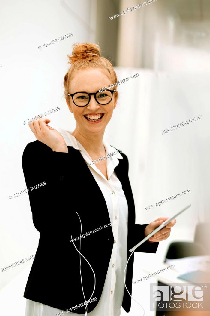 Stock Photo: Woman holding digital tablet in office.