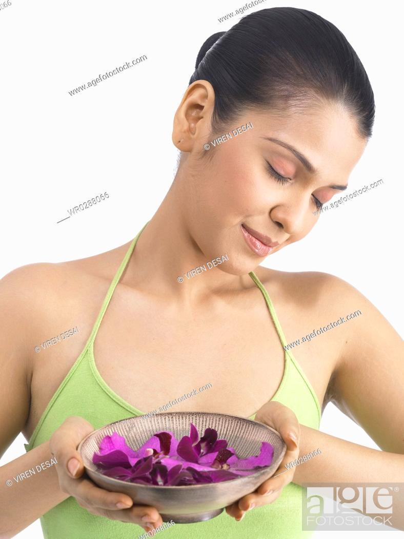 Stock Photo: South Asian Indian woman offering petals of mokara orchid flower wearing green dress MR 702.