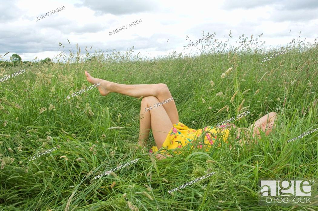 Stock Photo: Woman lying in field showing legs.
