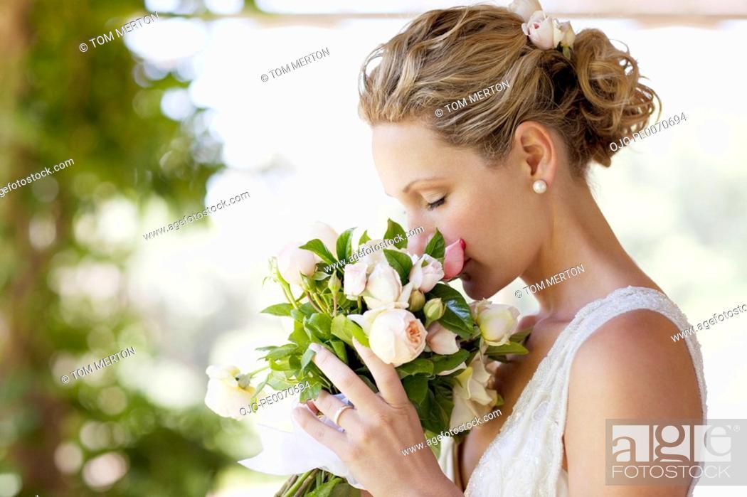 Stock Photo: Bride smelling bouquet.