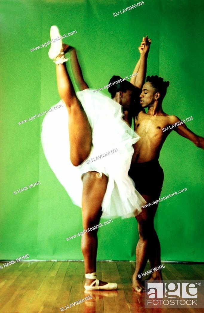 Stock Photo: Female ballet dancer holding hand of a male ballet dancer and raising her leg.