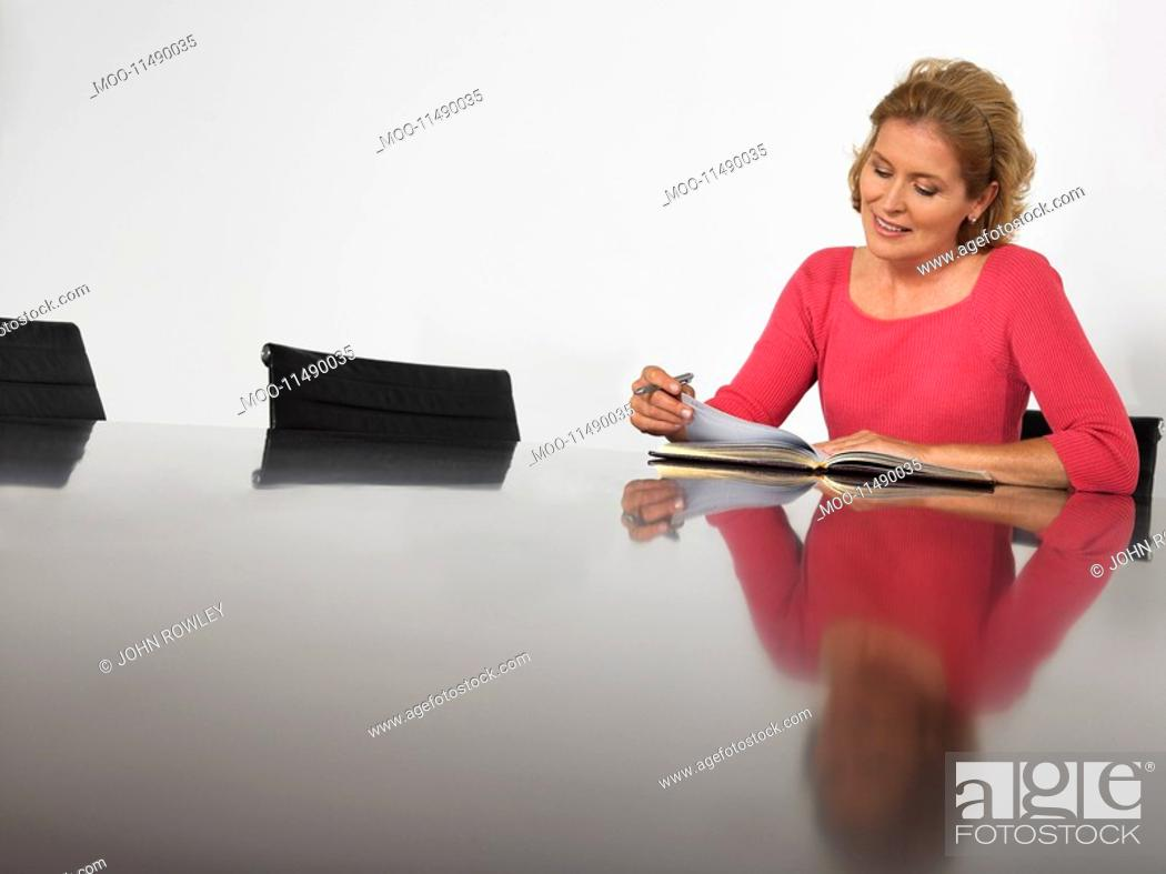 Stock Photo: Businesswoman reading in conference room.