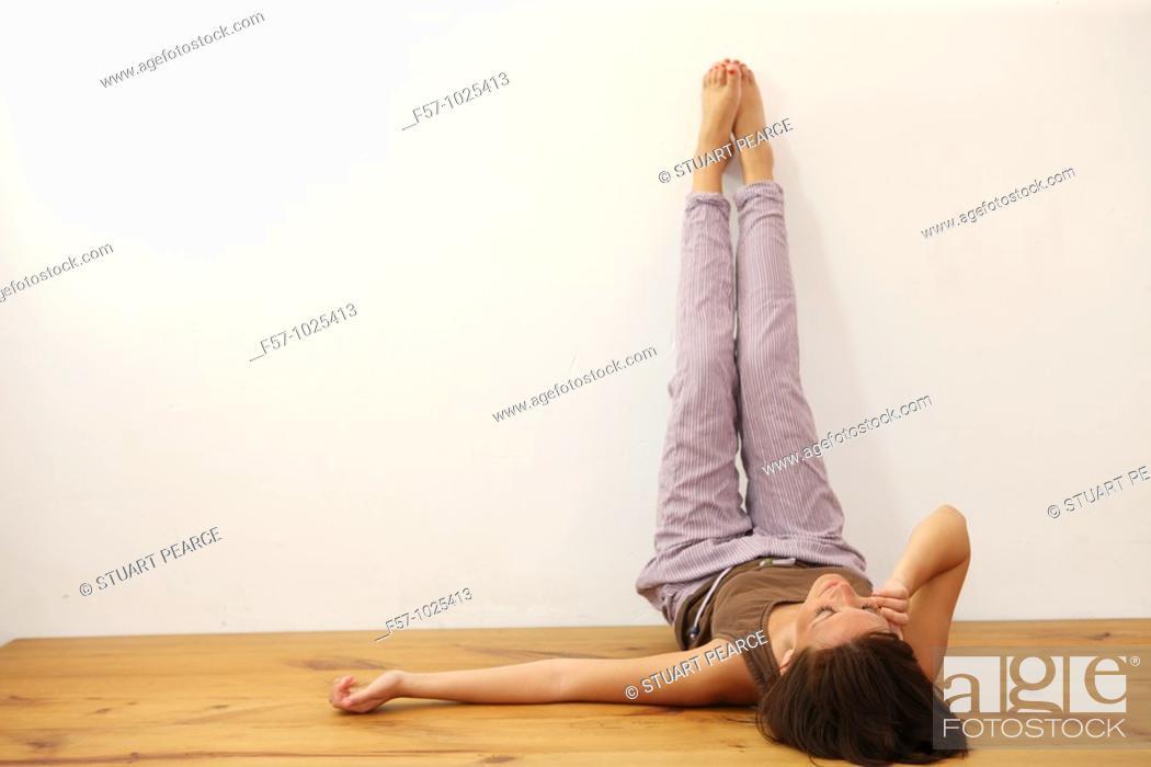 Stock Photo: Woman lying down, legs up.