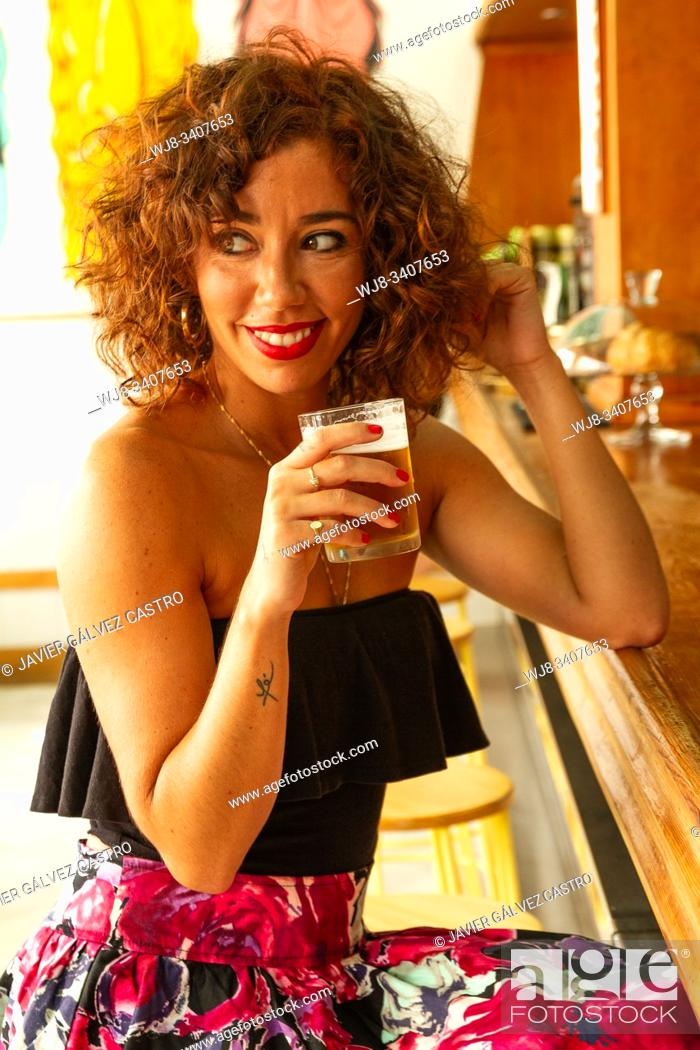 Stock Photo: Young woman looking to her right while holding a beer, smiling, wearing a black top.