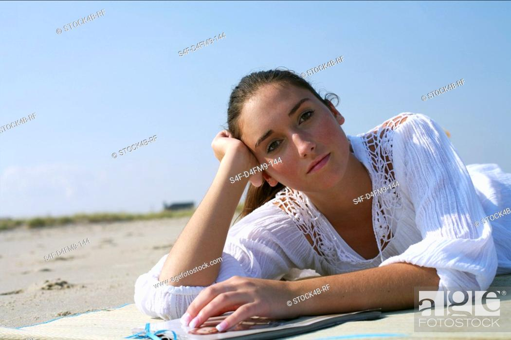 Stock Photo: Young brunette woman daydreaming at the beach.