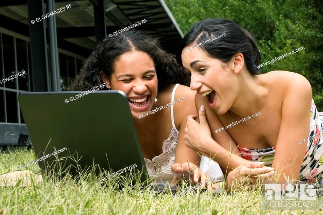 Stock Photo: Female university students working on a laptop and laughing.