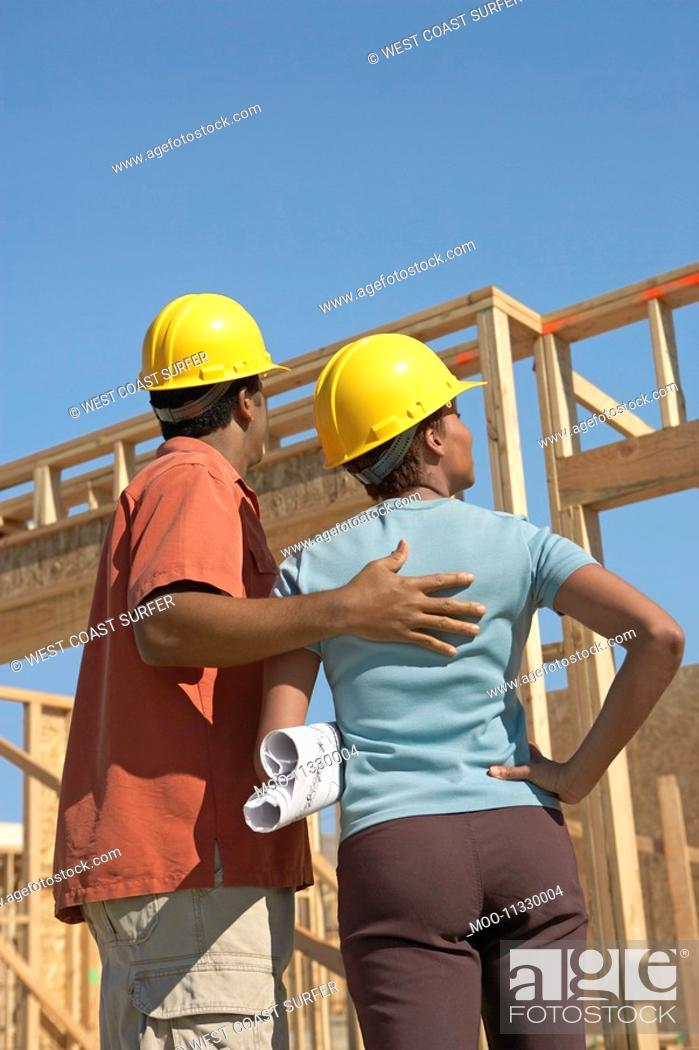 Stock Photo: Couple in hard hats on building site back view.
