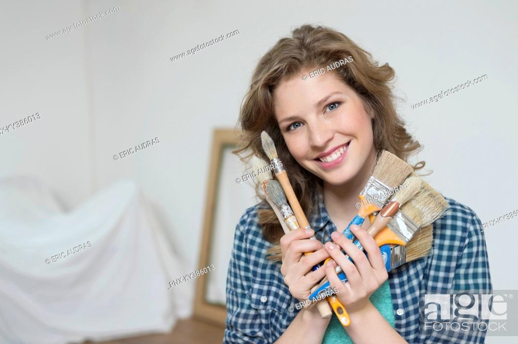 Stock Photo: Portrait of a woman holding paintbrushes and smiling.