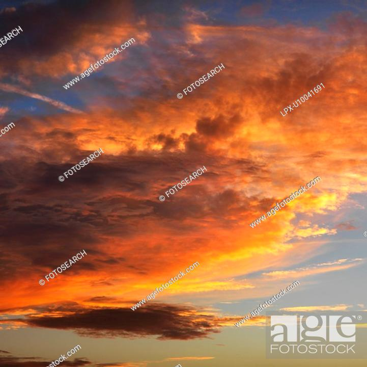 Stock Photo: Orange clouds in sky with sunset.