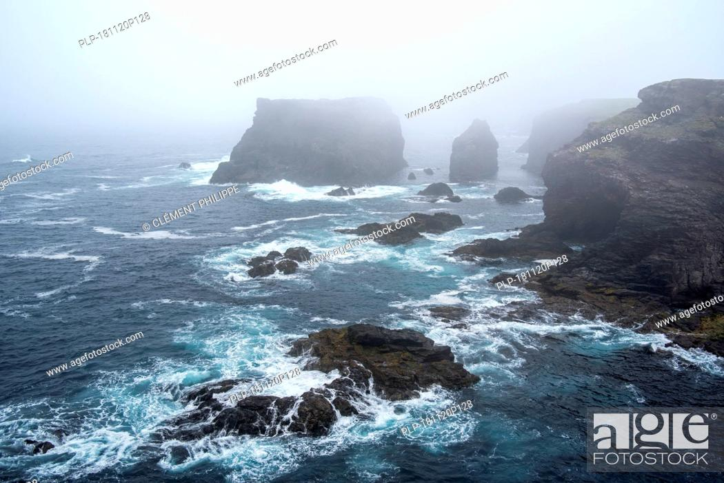 Stock Photo: Sea stacks and sea cliffs in mist during stormy weather at Eshaness / Esha Ness, peninsula in Northmavine, Mainland, Shetland Islands, Scotland, UK.