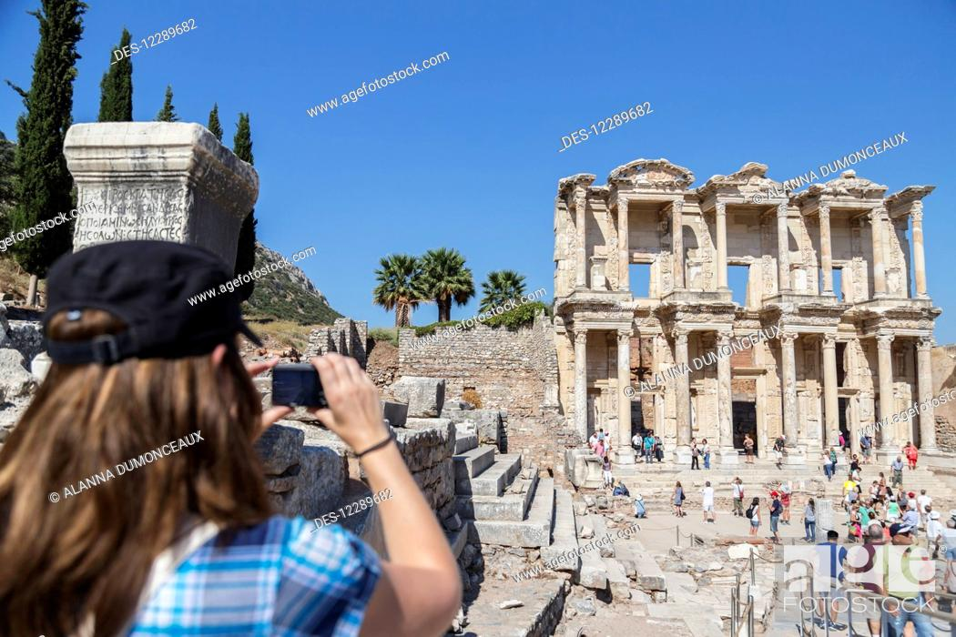 Stock Photo: A female tourist takes a photo of the Library of Celsus in the ruins of Ephesus; Ephesus, Izmir, Turkey.