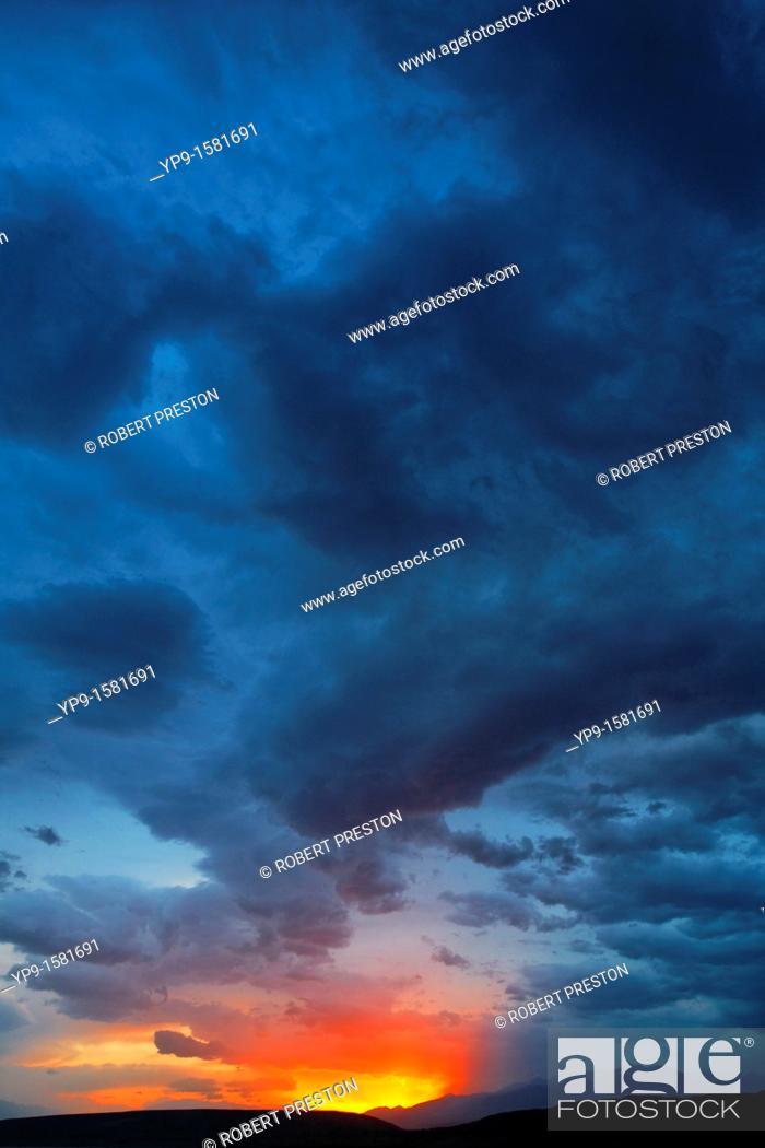 Stock Photo: Kyrgyzstan - Toktogul - stormclouds and sunset above mountains.