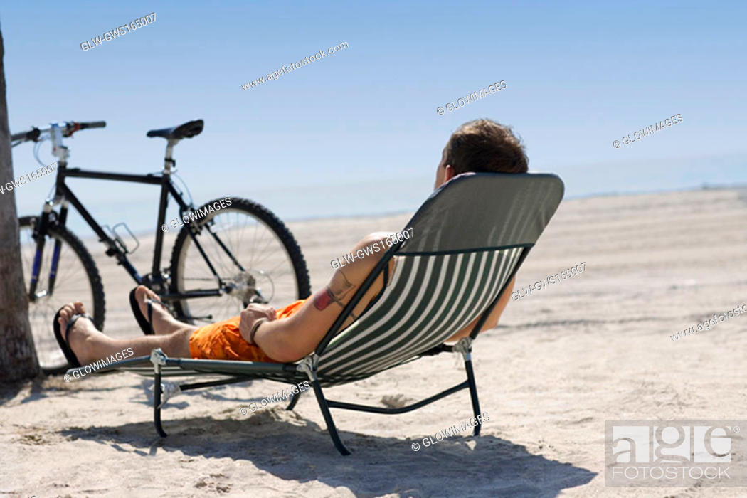 Stock Photo: Rear view of a man reclining on a lounge chair on the beach.