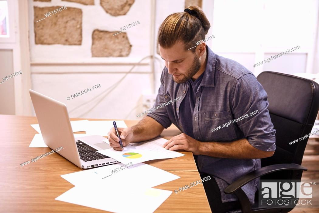 Stock Photo: Young businessman with his hair tied back sitting at his desk with a laptop making notes on a chart in front of him right handed.