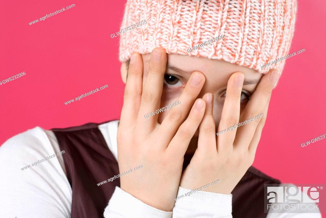 Stock Photo: Close-up of a girl hiding her face with her hands.