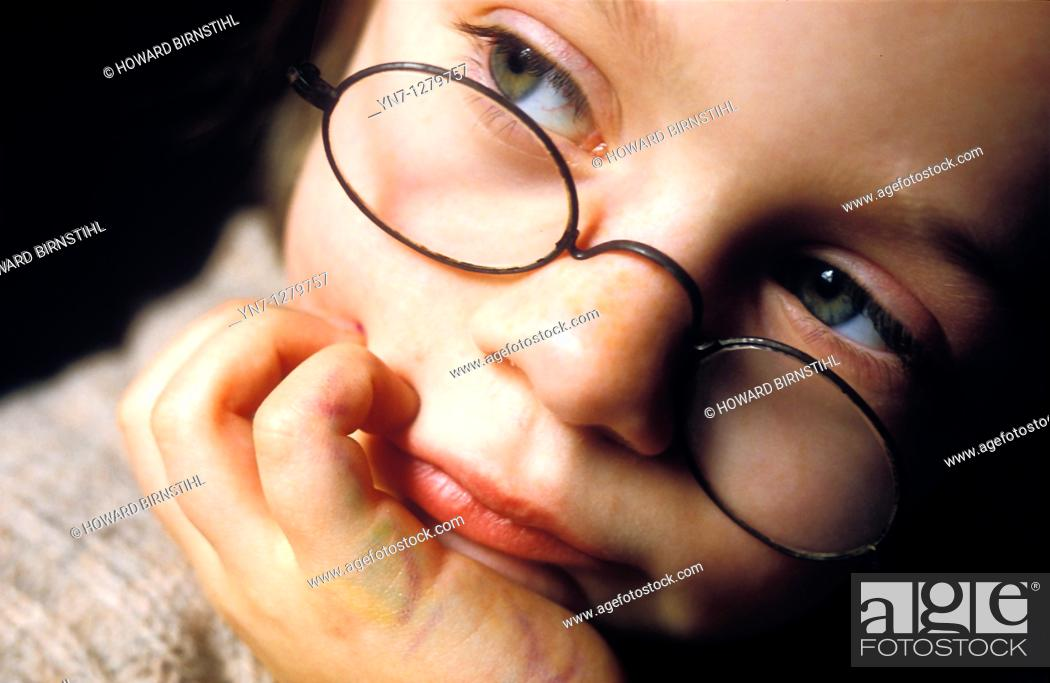 Stock Photo: child with glasses looking pensive.