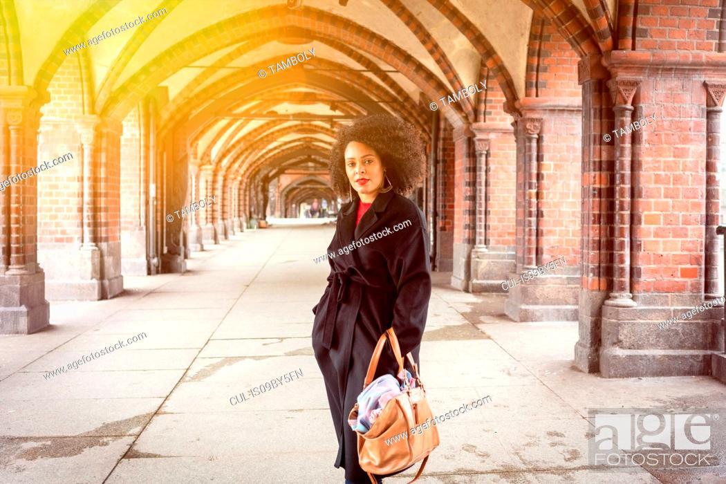 Stock Photo: Mid adult woman in stylish coat under archway of Oberbaum Bridge, portrait, Berlin, Germany.