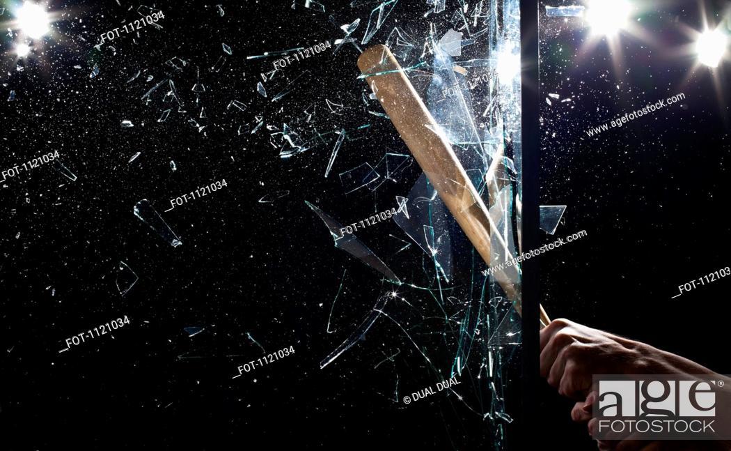 Stock Photo: Detail of a man smashing glass with a baseball bat.