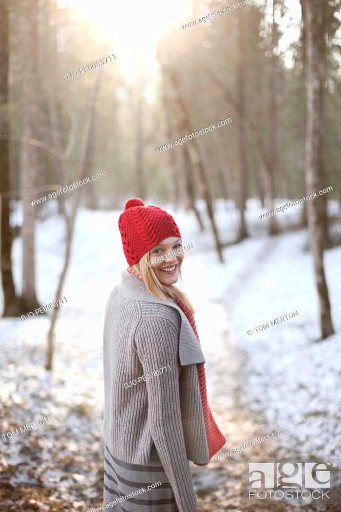 Stock Photo: Portrait of smiling woman walking in snowy woods.