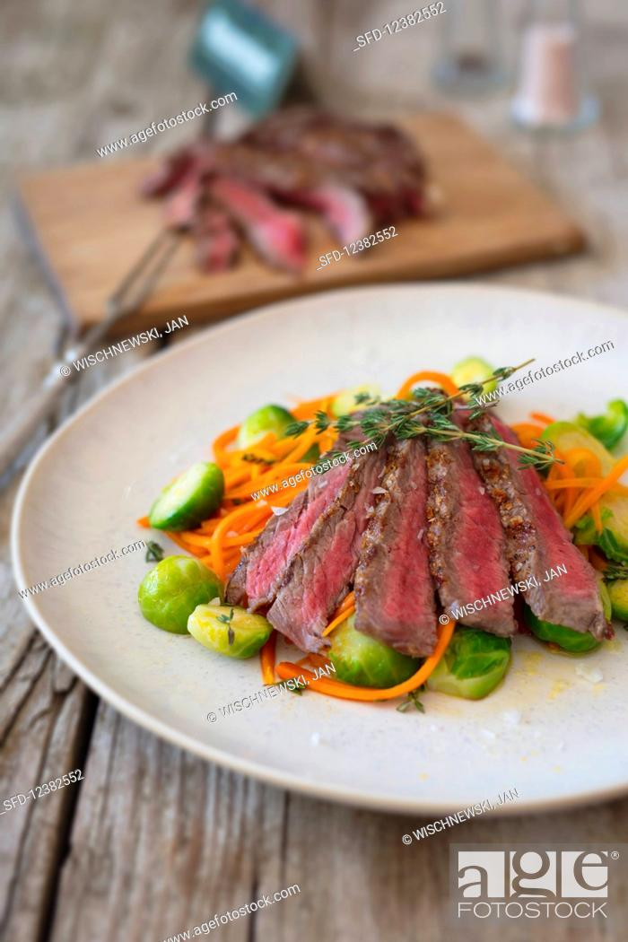 Imagen: Flank steak in strips with carrot noodles and Brussels sprouts.