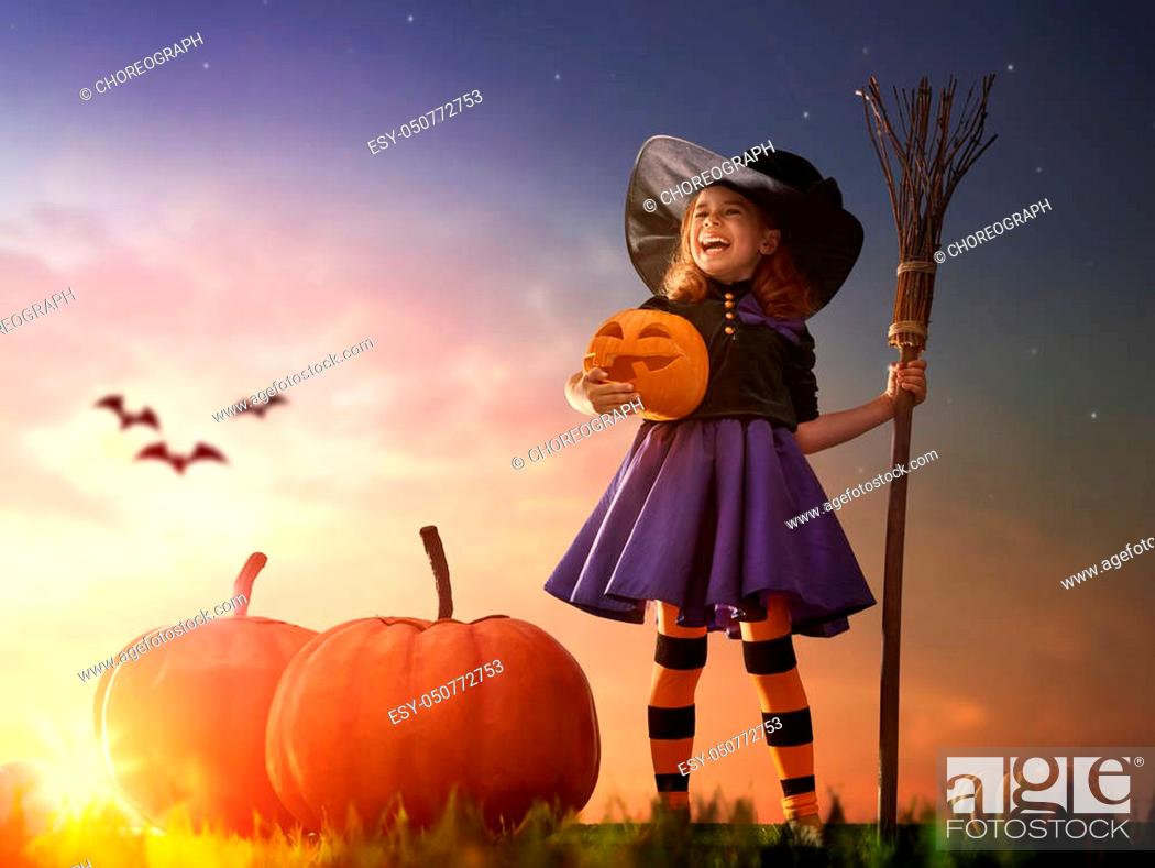 Stock Photo: Happy Halloween! Cute little witch with a big pumpkin. Beautiful young child girl in witch costume outdoors.