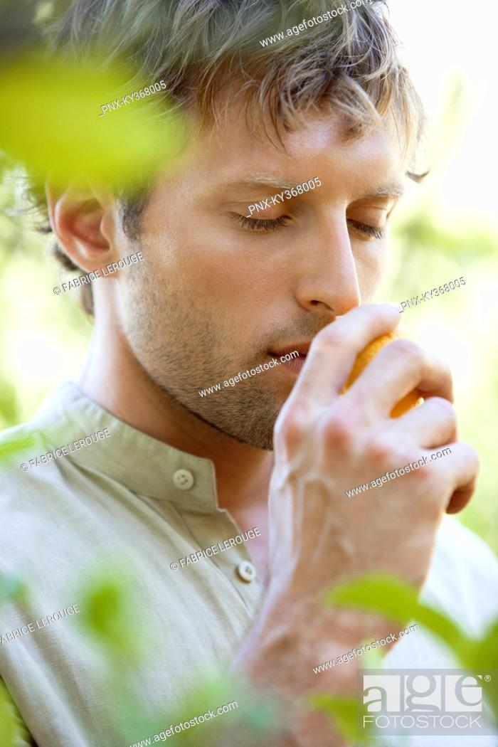 Stock Photo: Close-up of a man smelling a lemon.