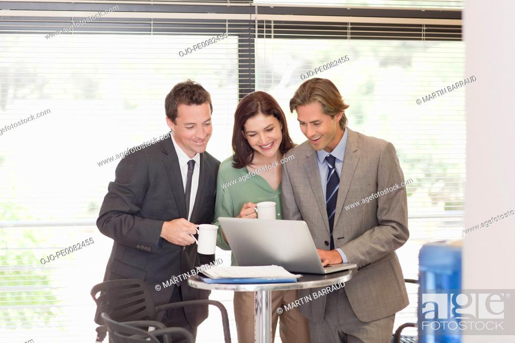 Stock Photo: Business people drinking coffee at laptop.