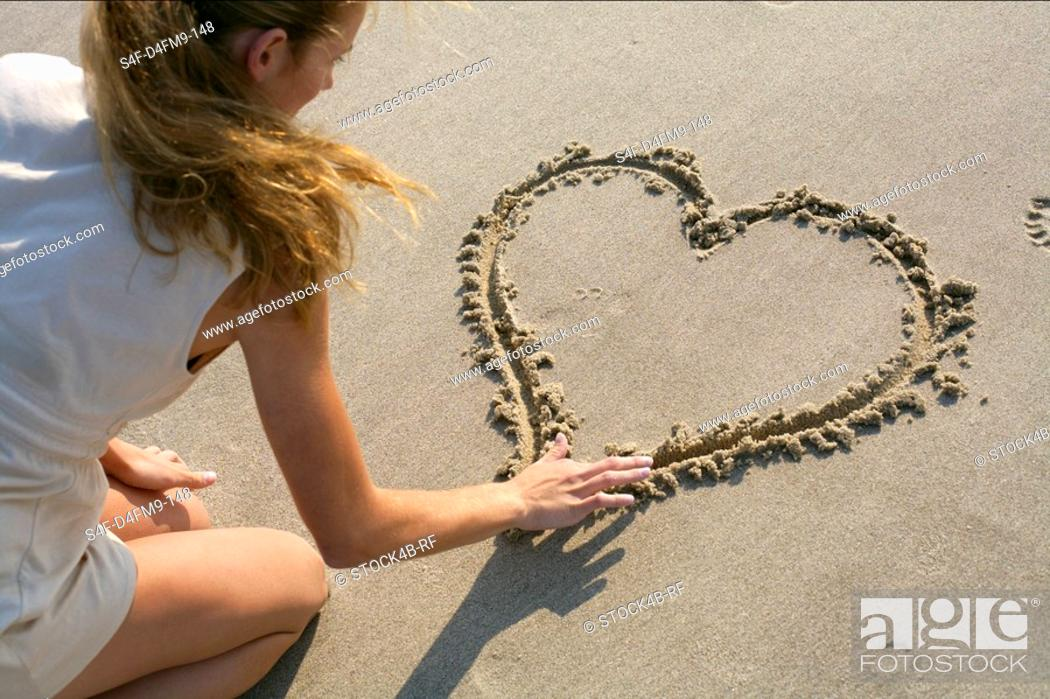 Stock Photo: Blond woman painting a heart into the sand with her finger, high angle view.