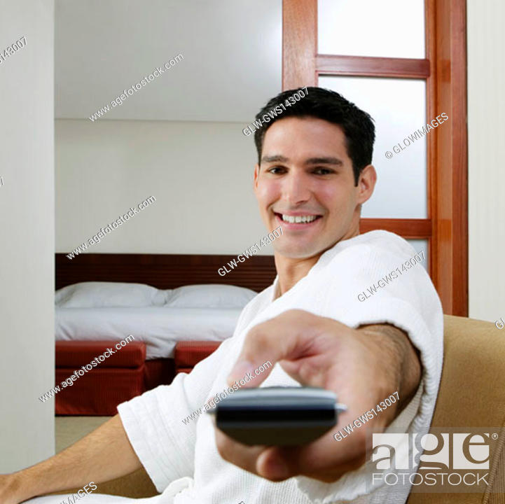Stock Photo: Portrait of a young man using a remote control and smiling.
