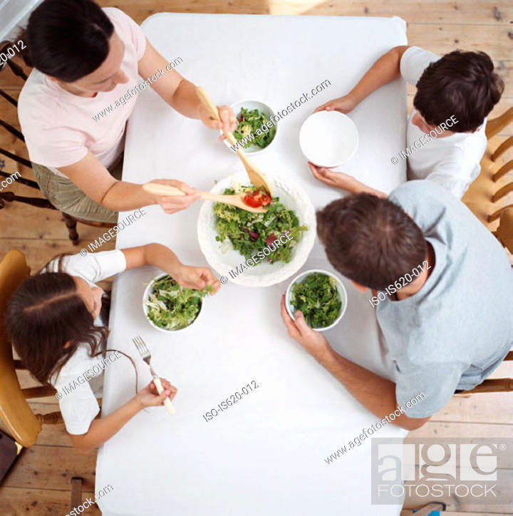 Stock Photo: Family eating salad at table.
