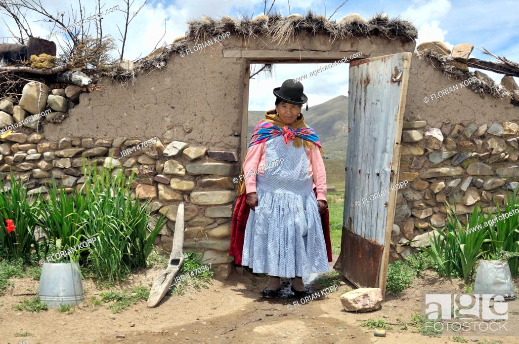 Stock Photo: Portrait of a woman in traditional dress of the Quechua in a yard gate, Bolivian Altiplano highlands, Departamento Oruro, Bolivia, South America.