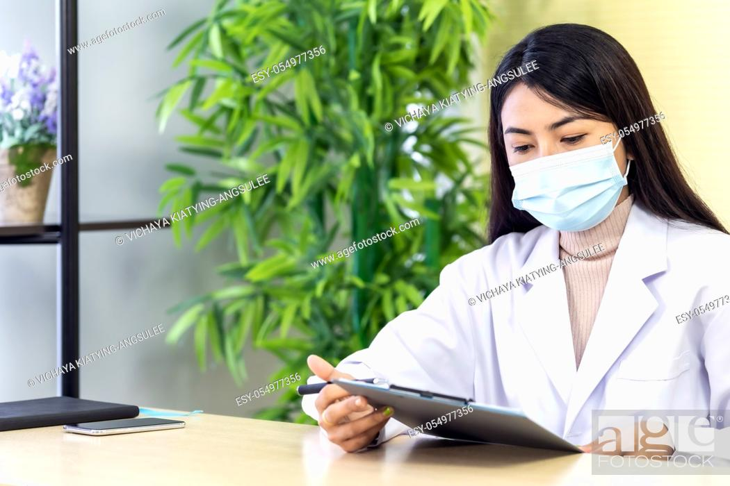 Stock Photo: Portrait of asian female doctor wear protective face mask sit in her office room in hospital clinic and reading on patience file before checking patience.